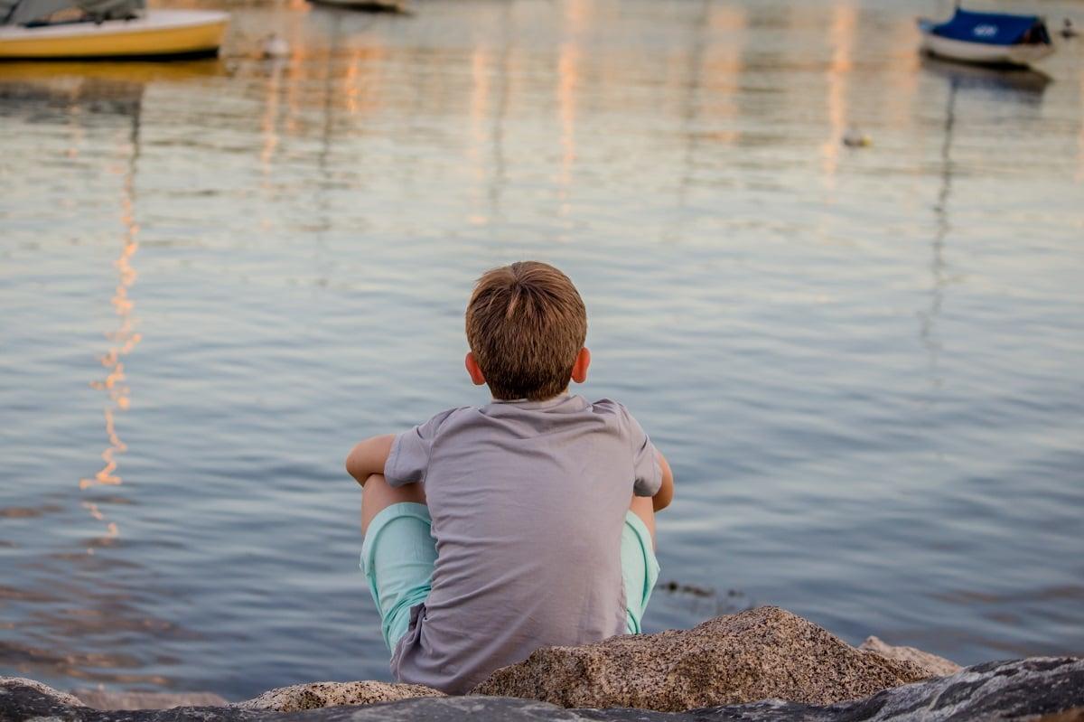 Jeune garçon de dos au bord de l'eau