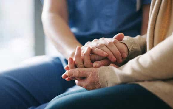 Main d'une personne âgée qui montre des signes de fin de vie