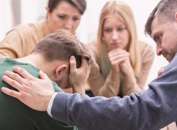 Personnes qui entourent un homme après un deuil au travail.