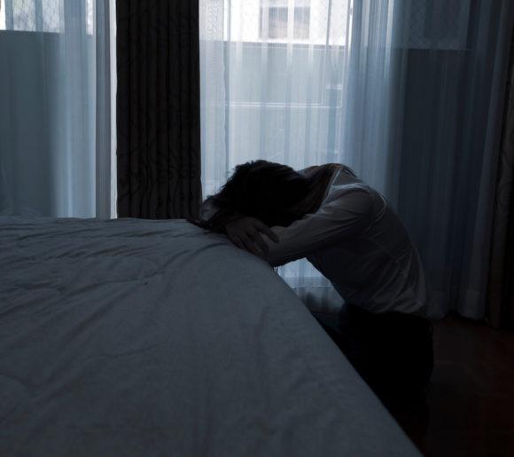 Une personne souffrant d'un deuil pathologique pose la tête sur son lit